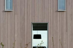 Die graue vertikale Schalung aus Weißtannenholz prägt das Äußere der Gebäude<br />