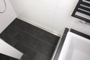 Das Hauptbadezimmer ist in Weiß-anthrazit gehalten. Die Duschrinnen-Abdeckung bildet einen spannenden Kontrast zu den Fliesen