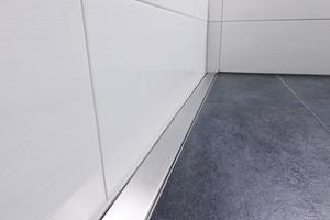 Bündig entlang der Wand verläuft die Rinne bis zur eingefassten Badewanne