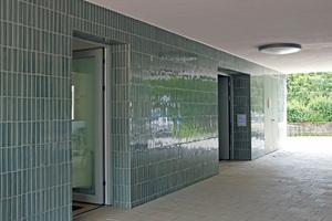 Die Durchgänge der Gebäuderiegel sind vollflächig gefliest. Durch den Spiegeleffekt erhöht sich die Lichtintensität