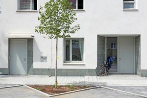 Details ästhetisieren die Straßenfassade: Die schräg ausgeführten Laibungen der Eingänge sowie der Sockelbereich sind wartungsarm gefliest