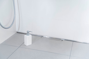 Die Dusche entwässsert über den schmalen Streifen an der Wand