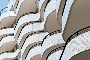 Die weißen, unregelmäßig perforierten Brüstungsbänder aus Metall umgeben das Gebäude und wölben sich im Bereich der geschossweise versetzten Balkone nach außen