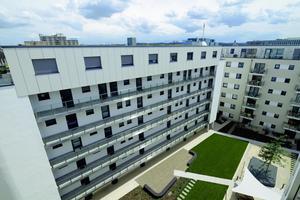 Das Staffelgeschoss mit den Maisonette-Wohnungen wird durch die Metallfassade in Weißmetallic betont