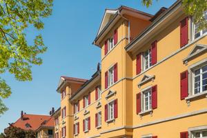 Wie ein Zwilling des Gebäudes gegenüber wirkt dieses Eckhaus im Spessartring 16 auf den ersten Blick. Doch es gibt einen feinen Unterschied: die Farbe der Holzklappläden. Auf dieser Straßenseite sind sie rot