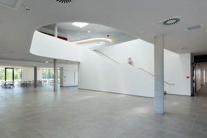 Von einem zentralen Aufenthalts- und Erschließungsbereich mitsamt zuschaltbarer Aula werden zwei Gebäudeflügel erschlossen