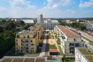 Links Bauteil C mit Tiefgarage, dessen (Hochbau-)Architektur an Stadtvillen erinnert. Das rechte Bauteil B schließt den Innenhof als geschlossener Gebäuderiegel zur Bahn und zur Straße ab