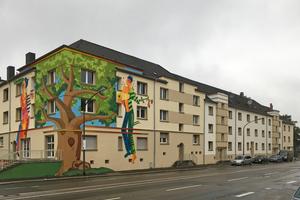 Die Fassadenmalerei am Bürgerbegegnungszentrum Storp 9 wurde nach der energetischen Sanierung vom Sohn des verstorbenen Künstlers nach Original-Vorbild erneuert