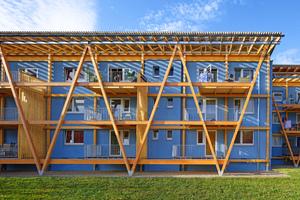 Wulsdorf: Der Wohnblock erhielt neue Balkone zur Gartenseite und besticht durch seine freundliche, hellblaue Farbigkeit, die einen Kontrast zum warmen Holzton bildet.