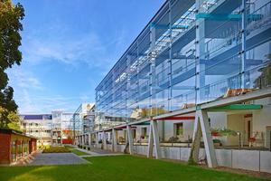 Klushof: Ein im Innenbereich an der Fassade fixiertes und vorgestelltes gläsernes Laubengangsystem ersetzt mit zwei Aufzügen sieben Treppenhäuser in der Wohnanlage