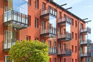 Klushof: Die rote Farbigkeit der Außenfassade zur Straße bezieht sich auf die historischen Backsteinbauten in der Nachbarschaft. Außerdem ergänzen Wintergärten den Wohnraum