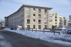 Straßenansicht eines der Gebäude; in der Farbgebung dominieren miteinander harmonierende beige-graue Töne
