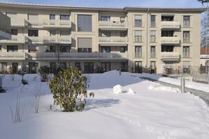 Hofansicht eines der Gebäude; die Fassadengestaltung mit zurückspringenden Fensterfaschen und unterschiedlichen Putzfassungen wird durch individuell gestaltete Balkongitter ergänzt