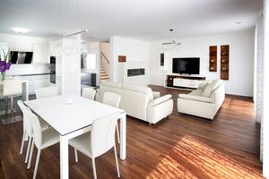 Im Inneren dominieren weiße Wände und Möbel, die mit dem dunklen Holzboden harmonieren
