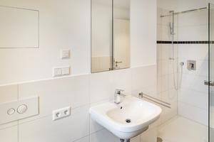 Die Bäder der Wohnungen sind unter anderem mit bodengleichen Duschen und fest eingebauten Spiegelschränken hochwertig ausgestattet