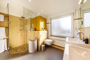 Eine gläserne Dusche, großformatige Spiegel und Wandverkleidungen aus Glas verleihen dem Badezimmer das gewisse Etwas