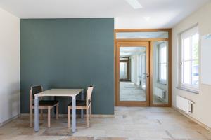 Im Eingangsbereich harmoniert ein hochwertiger, warmtoniger Steinboden mit der strukturierten Akzentwand im Metallic-Look
