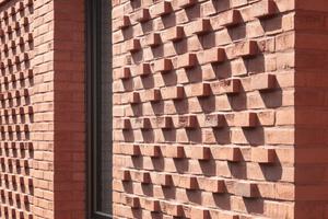 Die heraustretenden Köpfe brechen die Fassade auf und erzeugen eine gewisse Dynamik