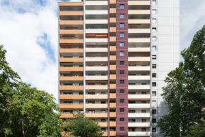 Grau-, Orange- und Rotnuancen betonen die kubisch verschachtelte Architektur. Variierende Farbverläufe betonen die vertikalen Balkonreihen