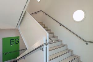 In kräftigen Farbtönen gestaltete Farbfelder bieten im ansonsten schlicht weiß gestalteten Treppenhaus Orientierung