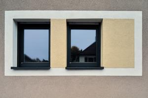Differenzierung mit Farbtönen und Putzstrukturen: Die weiße Umrahmung der Fenster setzt sich zusätzlich durch Feinputz ab. Diese sind kontrastierend mit Kratzputz gestaltet
