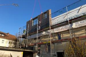 Per Kran werden die vorgefertigten Fassadenteile mit Lärchenholz-Verschalung in Position gebracht