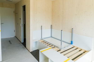 """Die 18 m² großen Appartements wurden voll ausgestattet auf der Baustelle <irspacing style=""""letter-spacing: -0.02em;"""">angeliefert. Die sichtbaren Holzinnenwände sind im Brandschutzkonzept durch</irspacing><irspacing style=""""letter-spacing: -0.015em;""""> </irspacing>Brandschutzmaßnahmen an den Außenwänden der Module kompensiert"""