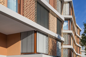 Die Fassade wird rhythmisiert in Abfolgen von lichtvollen, der Architektur folgenden Brauntönen. Zur Straßenseite hin schaffen eingestellte Metallelemente mit organischer Ornamentik eine lebhafte zweite Fassadenhaut
