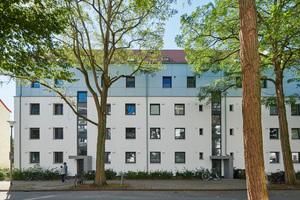 Die farblich und materiell abgesetzte Fassade der aufgestockten Gebäude lockert das Ensemble optisch auf zurückhaltende Art auf