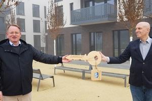 Corona-konform: Ingo Strugalla, geschäftsführender Vorstand der Stiftung Schönau (links), nimmt symbolisch den Schlüssel von Adam Vuletic von der BPD Immobilienentwicklung GmbH entgegen.