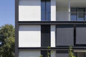 Die weiß abgesetzten Flächen stehen zur dunklen Farbe auf der Außenwärmedämmung in einem Kontrast und lockern das Gesamtbild der Wohnanlage auf