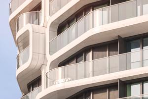 Wabenartige Loggia-Elemente strukturieren die vollständig verglaste Fassade