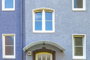 Die weiße Tür wird gerahmt durch die rote Backsteineinfassung und den Sockel. Der starke Hell-Dunkel-Kontrast betont die helle Tür, die optisch zu den weißen Fenstern und Faschen passt