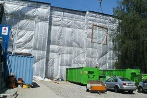 Vor dem eingerüsteten Richtergebäude wird ein demontiertes Fensterelement aus dem Sitzungssaalgebäude in einen Container abgelassen