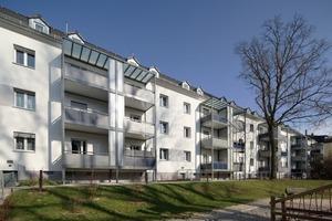 Die Hof- oder Gartenseite wird geprägt durch die neuen Vorstellbalkone. Die Grundfarbigkeit der Straßenseite – Grau und Weiß – herrscht auch hier vor, ergänzt um die grauen und petrolfarbenen Balkonbrüstungen