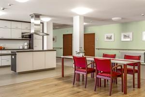 Der Aufenthaltsbereich wird durch den Bodenbelag wohnlich abgesetzt und die Bezugsstoffe der Stühle platzieren leuchtende Farbakzente im Raum. In den hellen Wandflächen sind die Türen und Handläufe deutlich wahrnehmbar, die Küchenzeile wird durch dunkle Einfassungen gegliedert