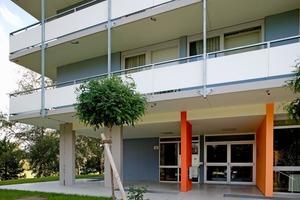 Hochhaus in Lahr: Eine orange Wandscheibe und rote Stütze markiert den Eingangsbereich des Wohnblocks<br />