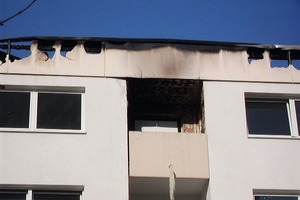 Auf einem Balkon im obersten Stockwerk traf in der Silvesternacht 2009 ein Feuerwerkskörper dort abgestellte Gegenstände. Die Flammen entfachten einen Brand, der das Dach und die oberen Teile der Fassade ruinierte Fotos (Brandschaden, Gerüst): Architekturbüro Wolfgang Barthel<br />