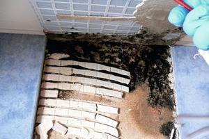 Bei Modernisierungen in Altbauten werden Bodenfliesen oft auf eine Spanplatte geklebt, die auf den alten Dielen liegt. Da die Konstruktion beim Begehen schwingt, bilden sich feine Risse in der Verfugung. Bade- oder Duschwasser sickert über die Jahre ein und führt zu einem intramuralen (versteckten) Schimmelschaden<br />