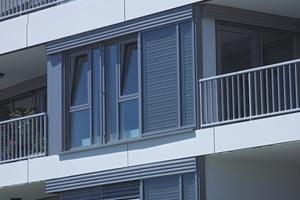 Fensterprofile, Geländer und außen liegender Sonnenschutz übernehmen die horizontale und vertikale Gliederung der Südfassade