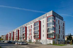 Acht rote Schallschutz-Erker gliedern die Straßenfassade der über 110 Meter langen Kirschgalerien