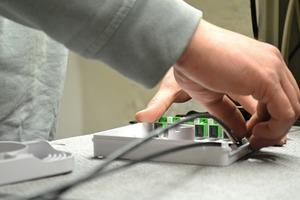 Glasfaserkabel, das über die Satellitenanlage unterirdisch an die Häuser gelangt, wird für die Weiterleitung in die Wohnungen und die anderen Häuser mit Spleißtechnik vorbereitet. Dabei werden die einzelnen Fasern in mehreren Arbeitsschritten entbündelt, gereinigt, abgetrennt und gespleißt