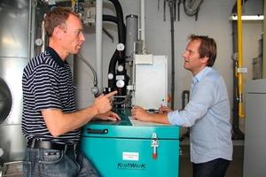 Wohnbau-Geschäftsführer Ralf <br />Petzold (l.) und ESM-Mitarbeiter Jörn Löffler überprüfen eines der modernen Blockheizkraftwerke <br />in Mühlheim am Main<br />