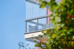 Geschützt von einem Glasvorhang bleibt der Balkon auch an kühleren Herbsttagen attraktiv, und die Möbel können das ganze Jahr über draußen bleiben