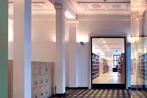 Die Eingangshalle mit ihrer stuckverzierten Decke, den Bodenfliesen und halbrunden Nischen wurde originalgetreu rekonstruiert, das große Glasfenster erlaubt den Blick in die moderne Bibliothekslandschaft