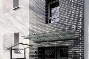 Die verklinkerten Treppenhäuser strukturieren den riegelförmigen Baukörper vertikal und verleihen den Bereichen um die Eingangstüren eine außerordentliche Robustheit
