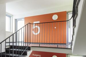 Neue Freundlichkeit, herzliche Atmosphäre und bessere Orientierung auch im Treppenhaus: Der Rotton der Fassadengestaltung wurde innen großformatig aufgenommen und variiert