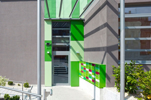 Eine graue Fassade mit moderner Eingangssituation besticht durch das Spiel mit grünen Akzentflächen. Die Übertragung der Grüntöne auf die Briefkastenanlage, ergänzt mit roten Akzenten, schafft einen frechen, frischen und unkonventionellen Eindruck