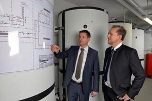 Andre Siegel (Junkers Bosch, links) und Ulrich Farwick (Vivawest) nehmen die Heizungsanlage in Betrieb. In den sechs Heizungspufferspeichern werden die Erträge aus den Solarkollektoren auf den Dächern gespeichert