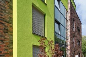 Die grüne Putzfläche dieses Wohngebäudes in Bielefeld schafft einen gelungenen Kontrast zur angrenzenden Klinkerfassade